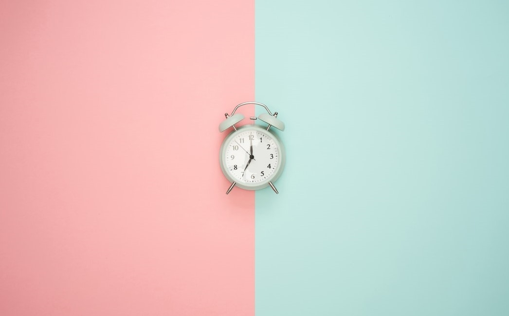 Alarm clock set against pink and green background