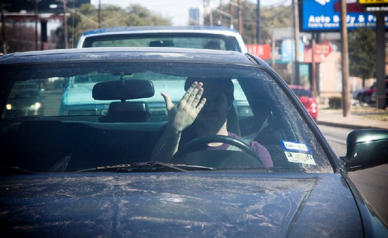 Man sat in dirty car waving hand in annoyed manner