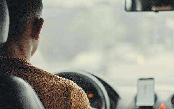 backseat view of a man driving