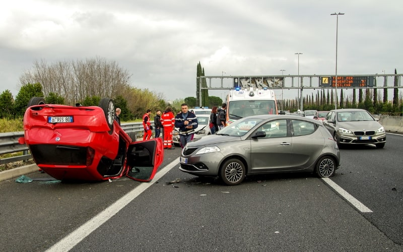 Car accident on a motorway, with one car overturned, with emergency responders in the background