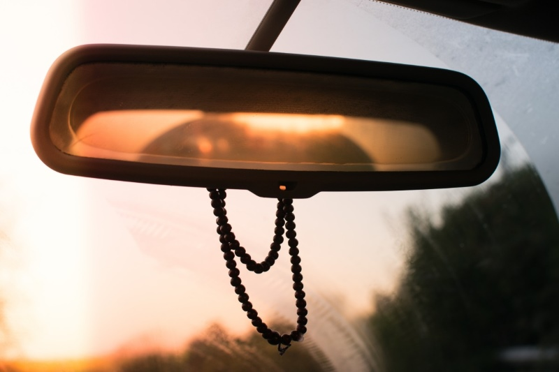 Interior car mirror with a string of beads attached