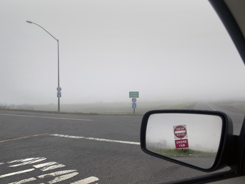 Foggy road with car mirror showing a reflection of a no entry sign