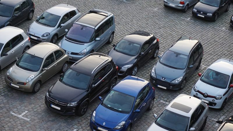 Photo of a car park with black, blue and grey cars taken from above