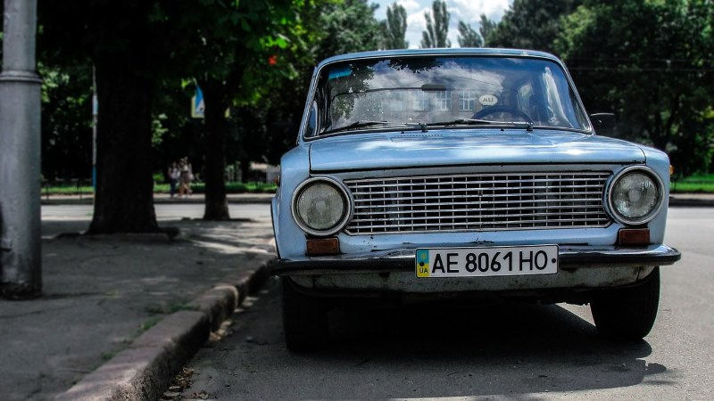 Car with Ukrainian licence plates parked next to a kerb by a park