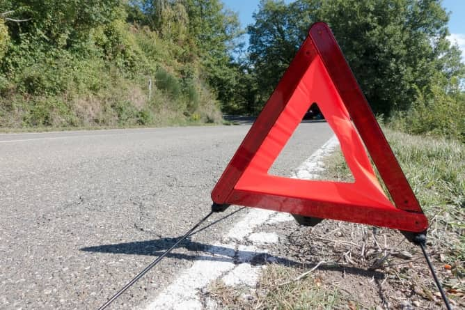 Red warning triangle placed at the side of a road