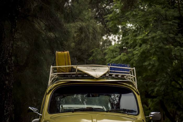 Car with roof rack holding surfboard and luggage