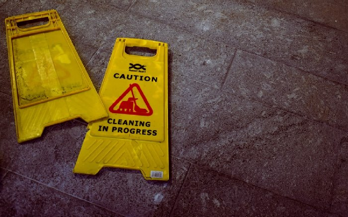 Two 'cleaning in progress' signs on floor