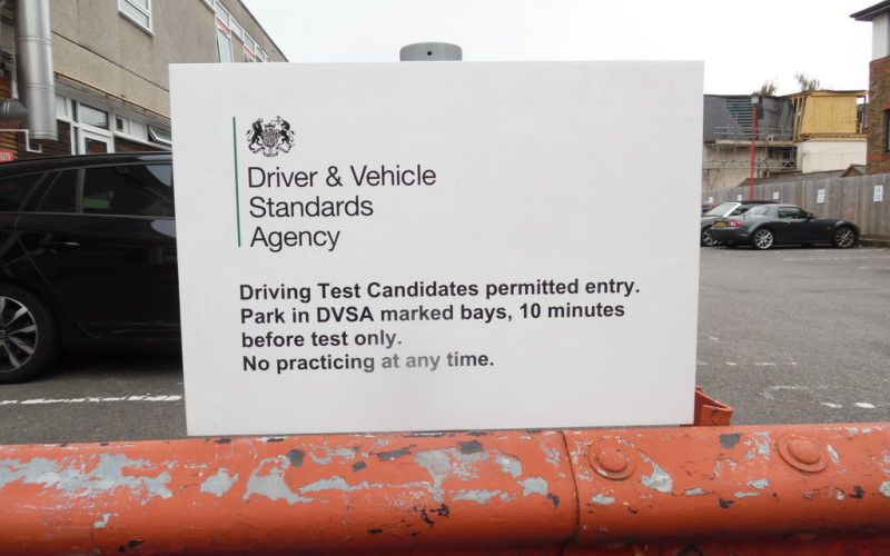 DVSA-branded sign outside a driving test centre car park in Hemel Hempstead. Warning on sign: Driving Test Candidates permitted entry. Park in DVSA marked bays, 10 minutes before test only. No practicing at any time.