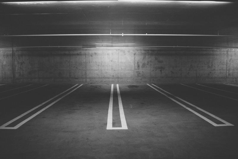 Grayscale photo of empty car parking spaces