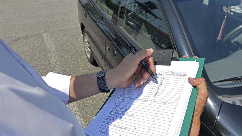 Examiner stood outside car marking driving test on a clipboard