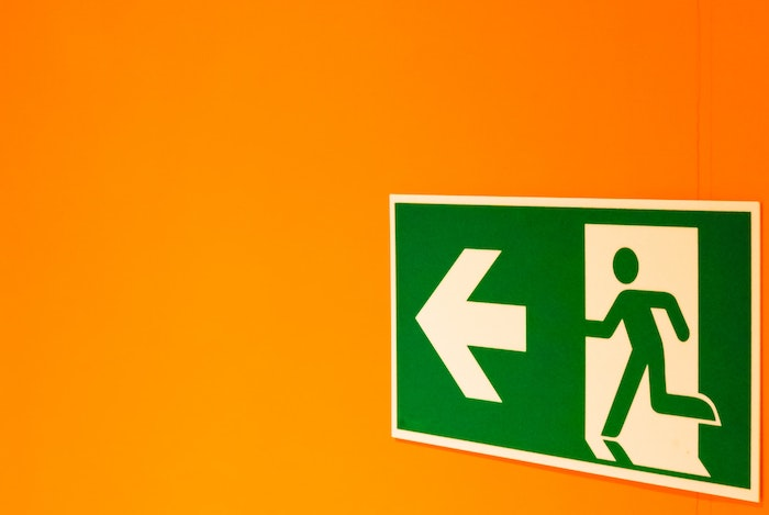 Green exit sign of figure running towards arrow on a yellow background