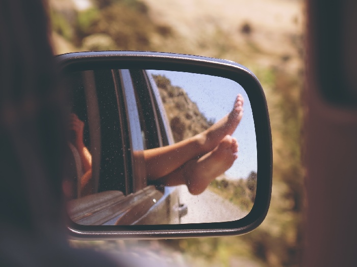 Bare feet poking out of car window seen through wing mirror