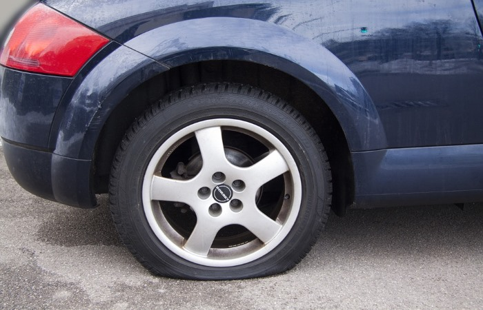 A dark blue car with a flat tyre
