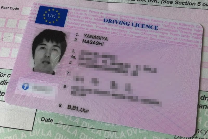 1998-style UK photocard driving licence lying on top of a paper counterpart licence