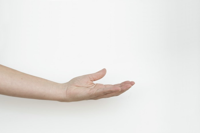 Hand outstretched against white background