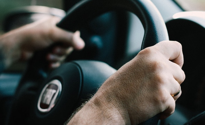 Hands holding a steering wheel