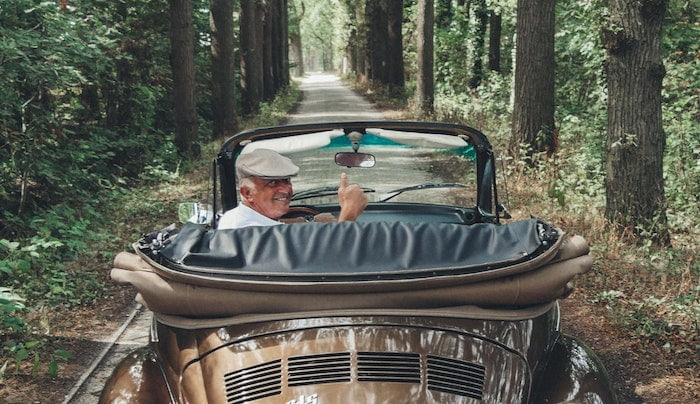 Old man giving thumbs up from vintage car in forest