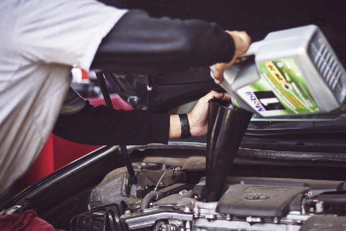Man topping up car liquids under bonnet