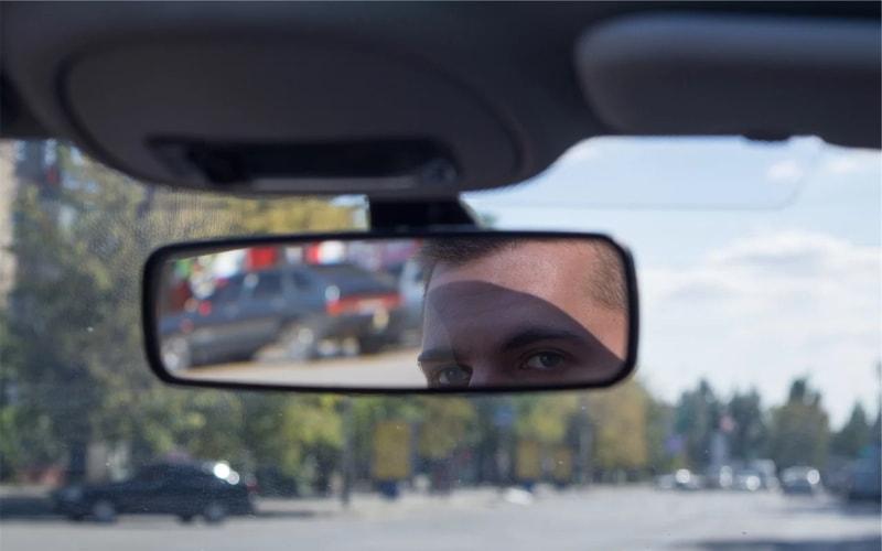 Man looking in car interior mirror