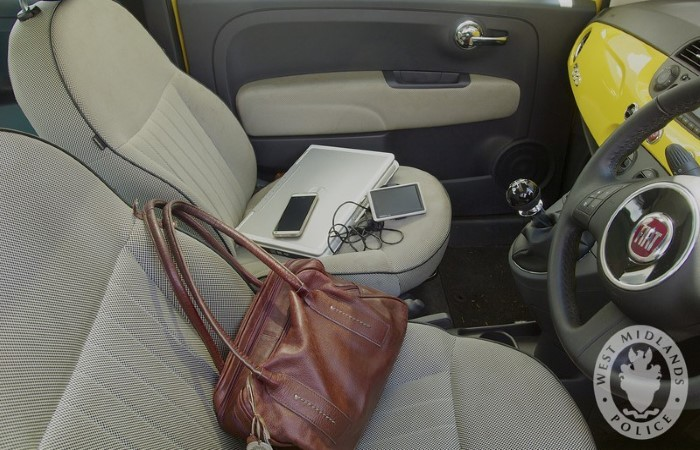 Belongings like a laptop and mobile phone out in the open inside a car
