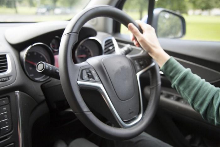 one hand on steering wheel