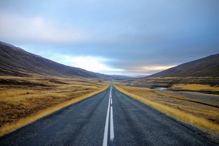 Long, straight, empty road with hills on either side