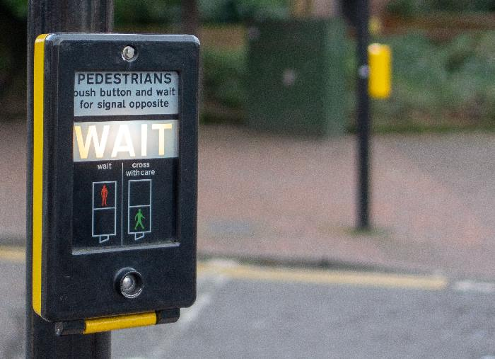Wait sign at pedestrian crossing