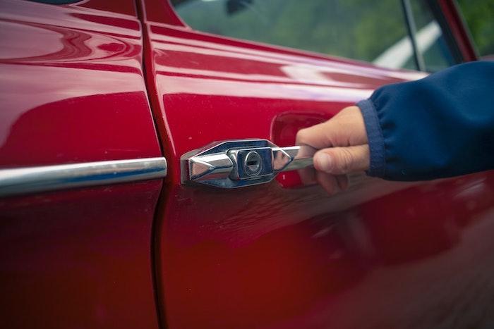 Hand opening door of red car