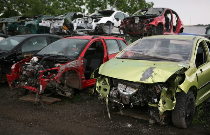 Scrapped red and green cars next to each other in a scrap yard