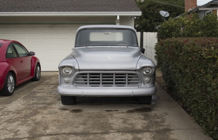 silver-vintage-car-parked-in-driveway-next-to-red-car