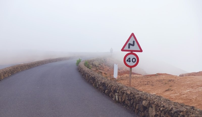 Speed limit and bend signs on a foggy road