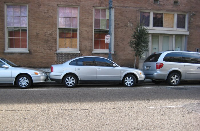 three-grey-cars-parallel-parked-outside-building