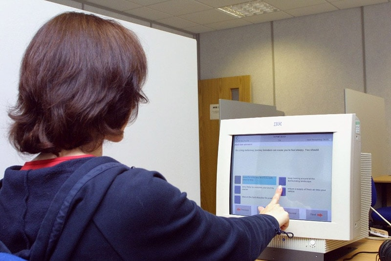Candidate answering theory test questions on a touch screen