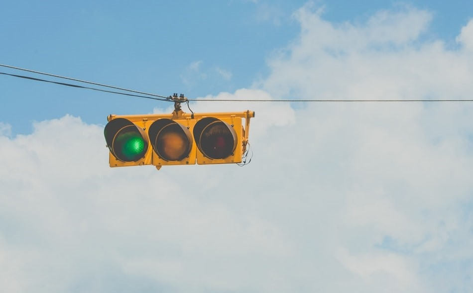 Horizontal yellow traffic lights on green hanging on wire against blue sky and clouds