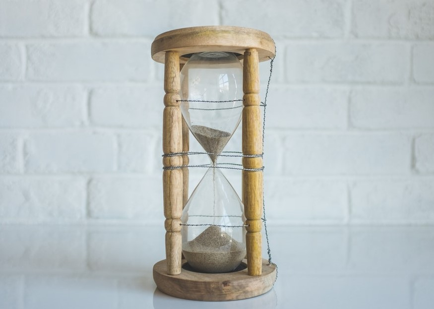 Wooden hourglass with white sand against white brick backdrop