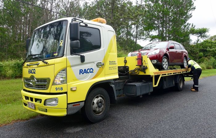 Yellow and white tow truck with a red car on the back