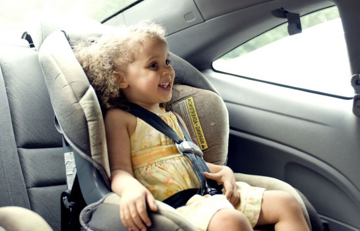 young girl in child car seat